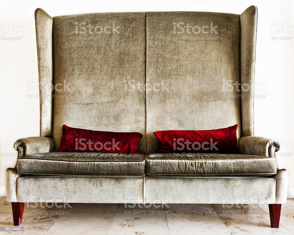 Designer couch in silver velvet with crimson pillows stock photo