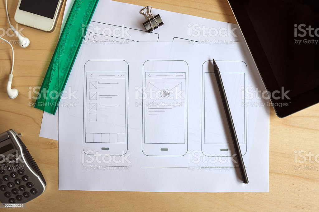 Designer desk with paper prototype of a mobile application stock photo