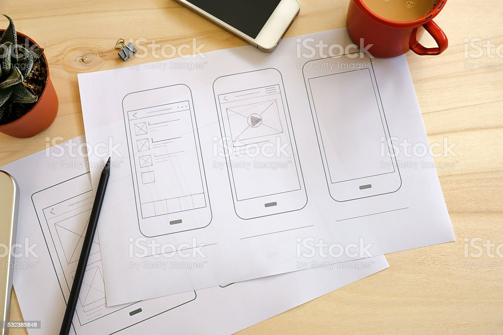 Designer desk with UI wireframe sketches stock photo
