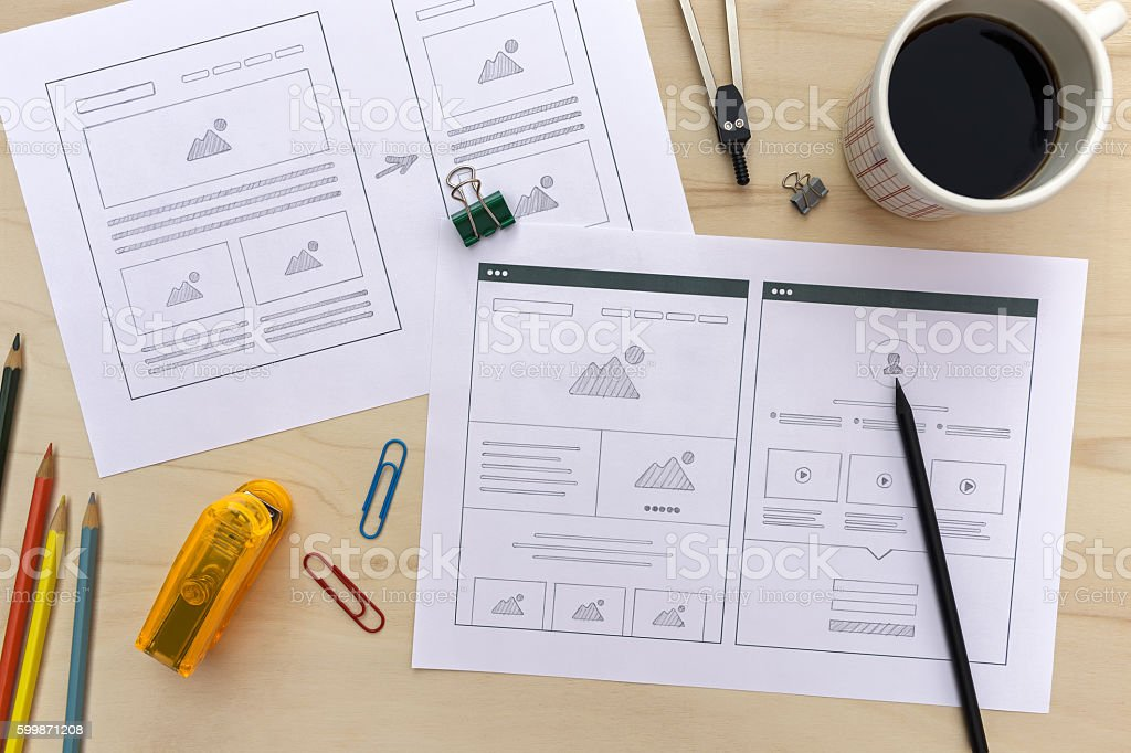 Designer desk with website wireframe sketches stock photo