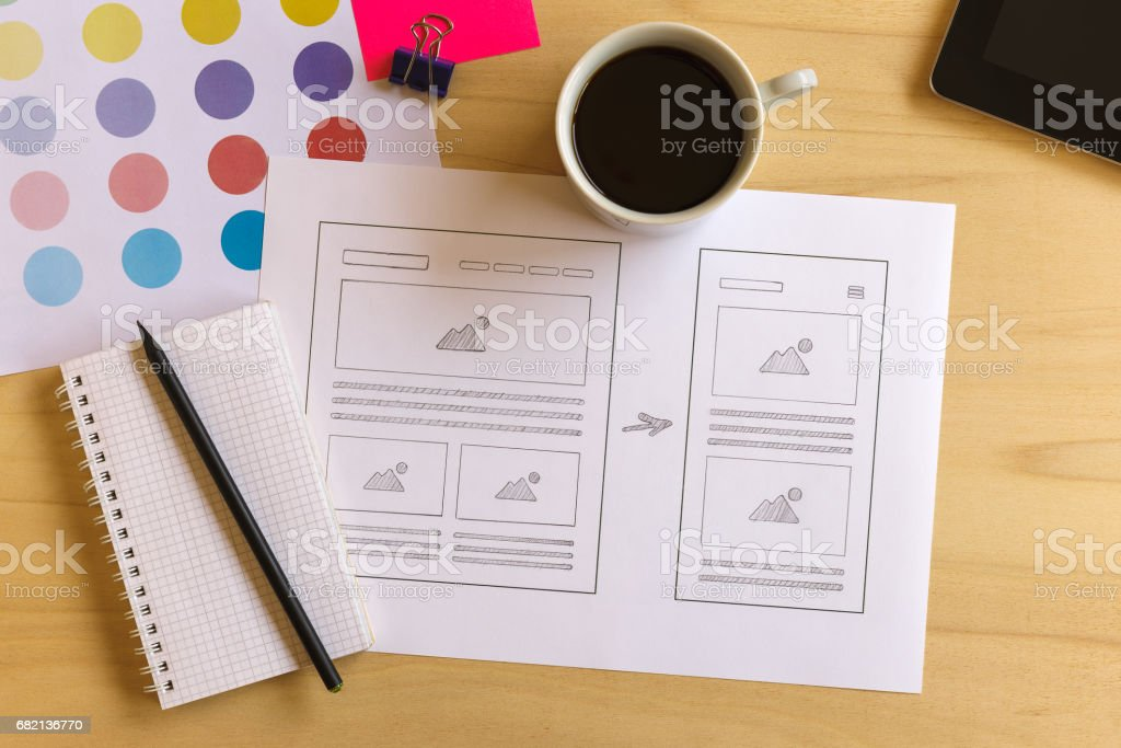 Designer desk with wireframe sketches for responsive website stock photo