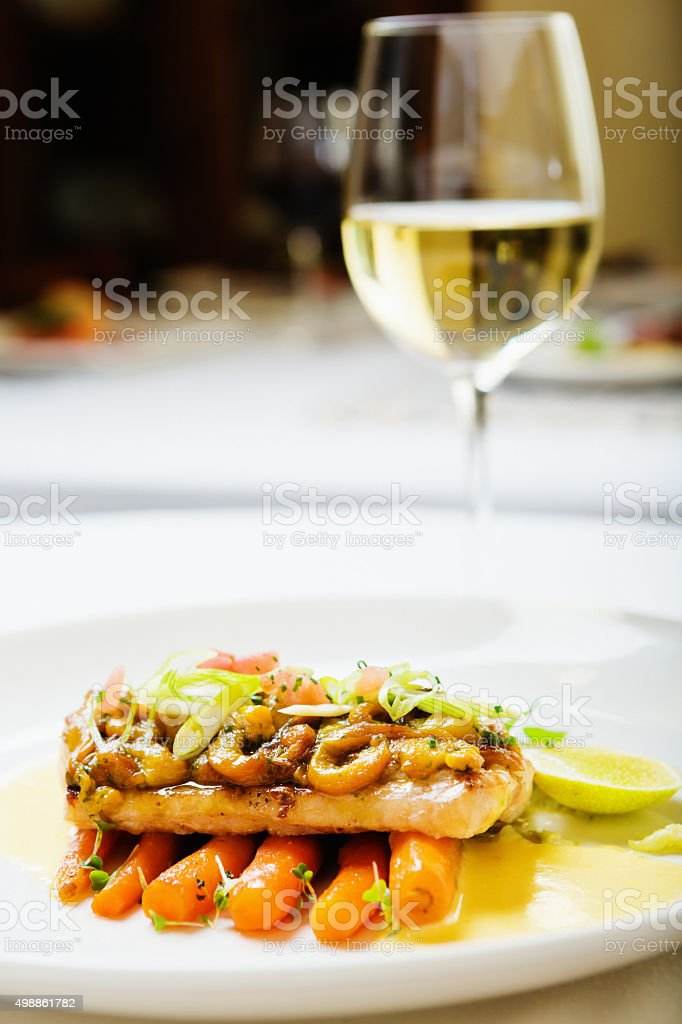 Designer dining: beautifully plated grilled fish dish with wine stock photo
