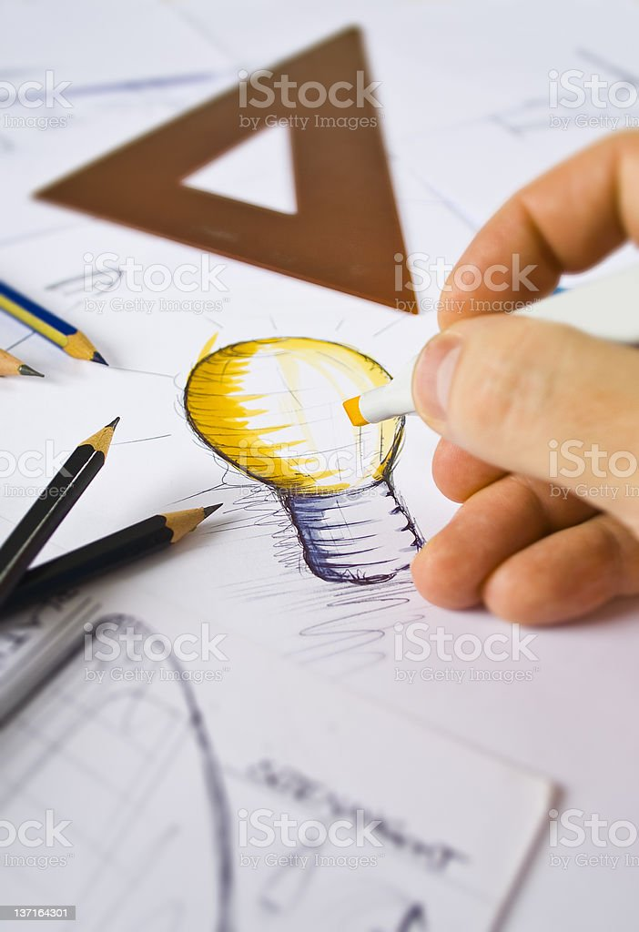 Designer drawing and coloring a light bulb stock photo