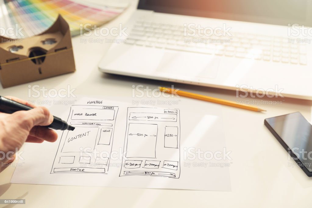 designer drawing website development wireframe on paper stock photo