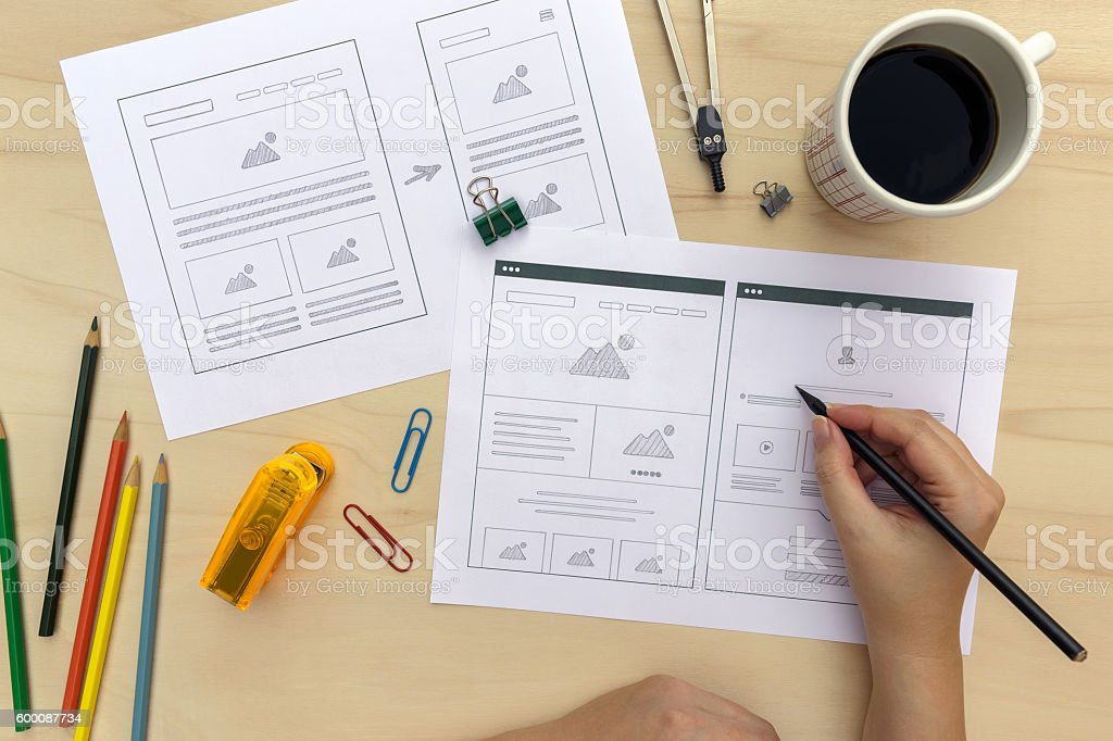 Designer drawing website wireframes on wooden desk stock photo