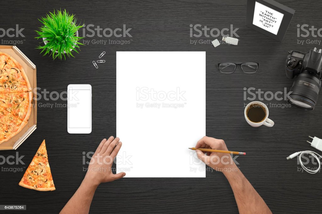 Designer or photographer sketching on empty white paper. Camera and mobile phone beside. Top view of black work desk. stock photo