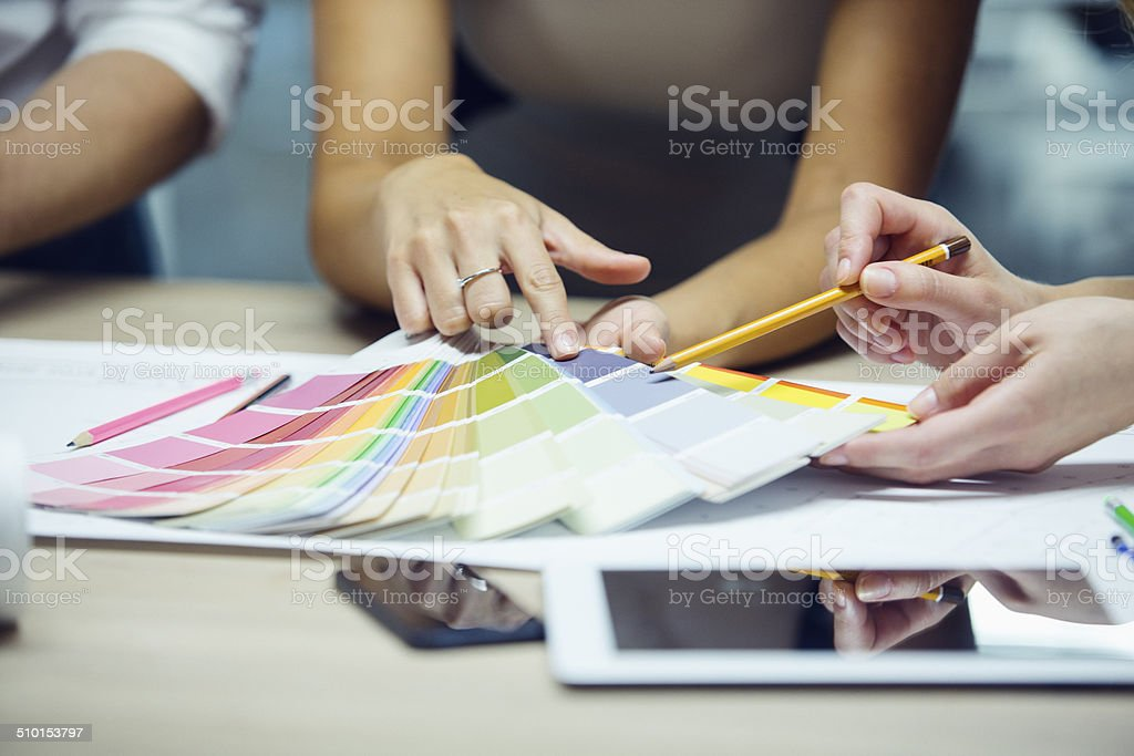Designer pointing to color swatch. stock photo