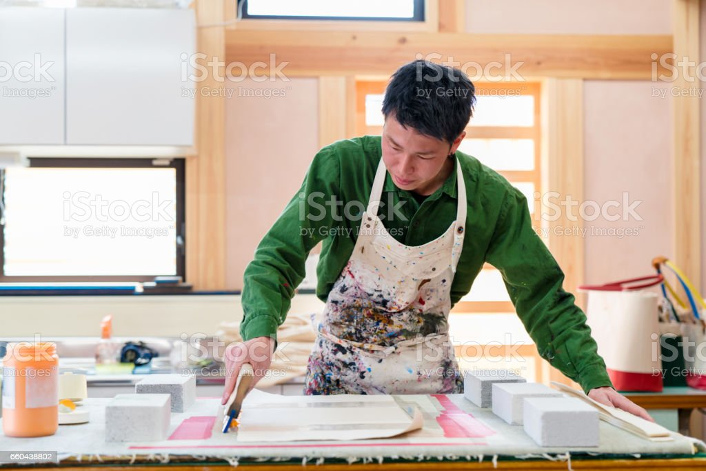 Designer screen printing onto fabric with a squeegee stock photo