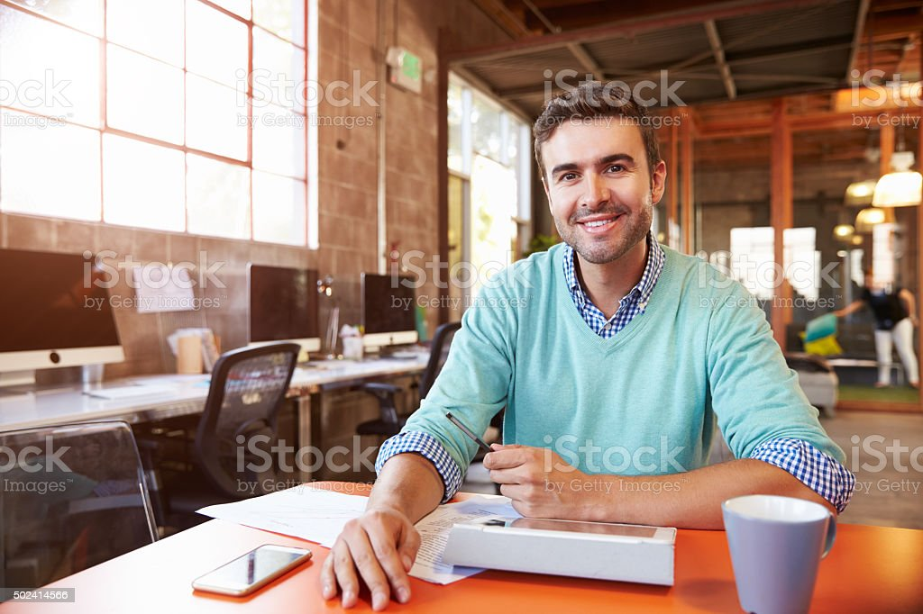 Designer Sitting At Meeting Table Working On Digital Tablet stock photo