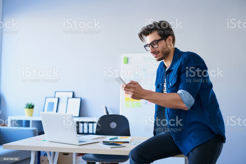 Designer sitting on desk in office using his smartphone stock photo