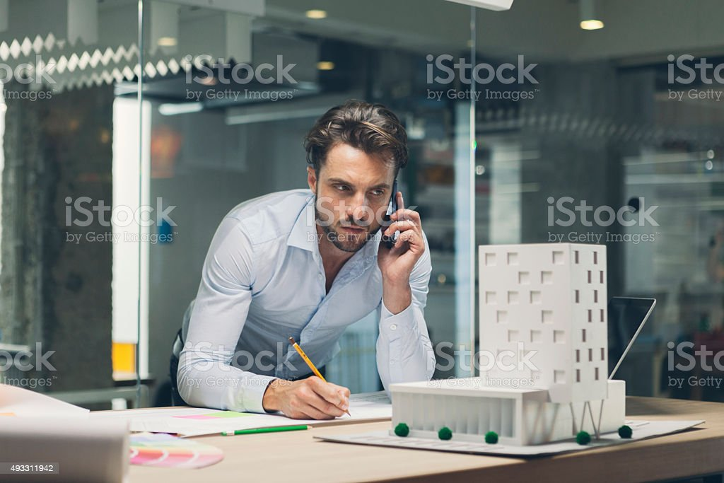 Designer talking on smart phone in office. stock photo