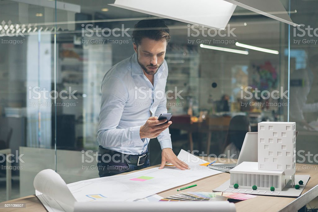 Designer typing on smart phone in office. stock photo