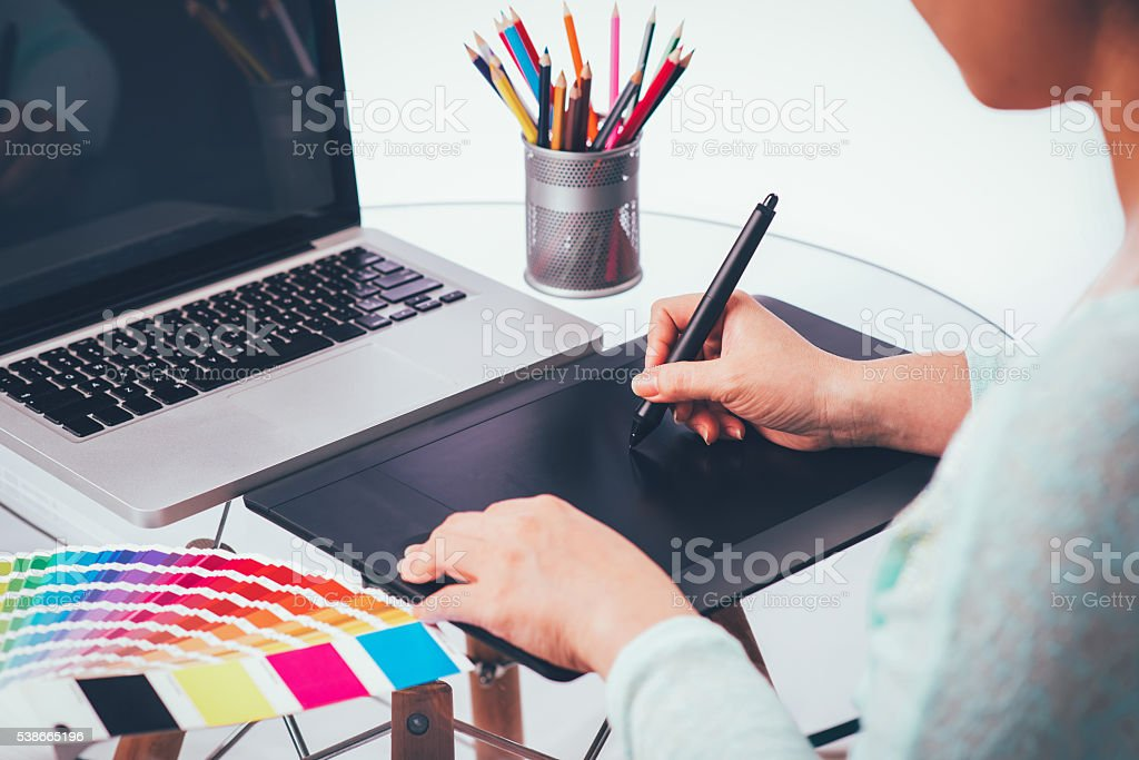 Designer using graphics tablet and colour charts stock photo