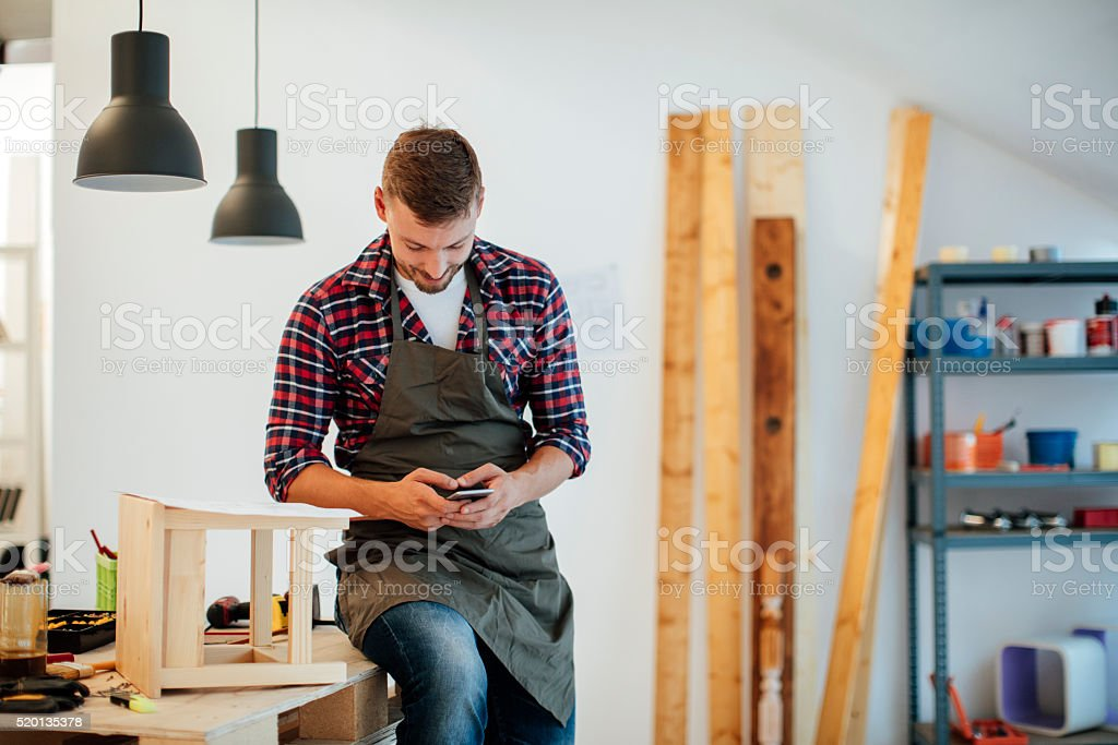 Designer Using Smart Phone In His Furniture Workshop. stock photo