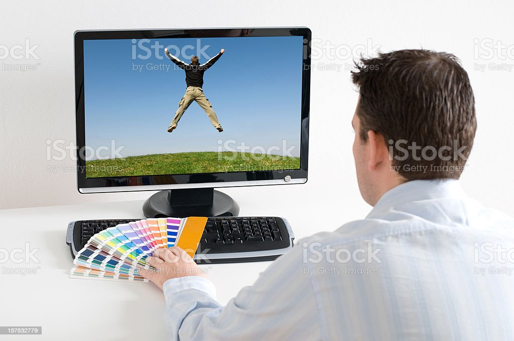 Designer works in front of computer using color picker royalty-free stock photo