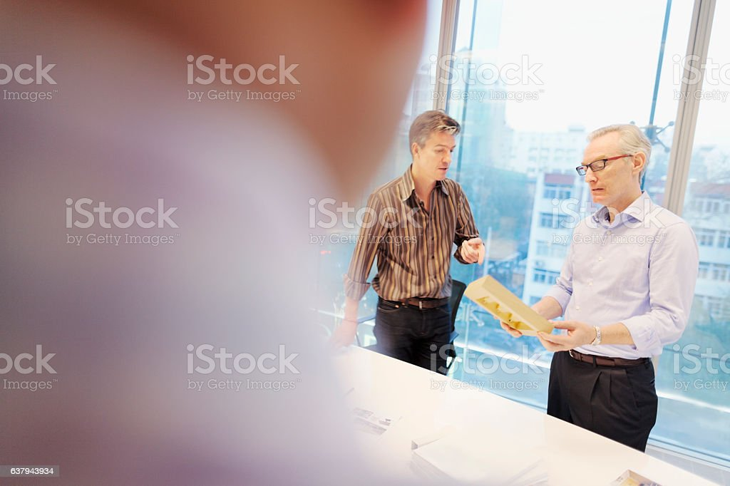 Designers discussing project planning with product sample in office stock photo