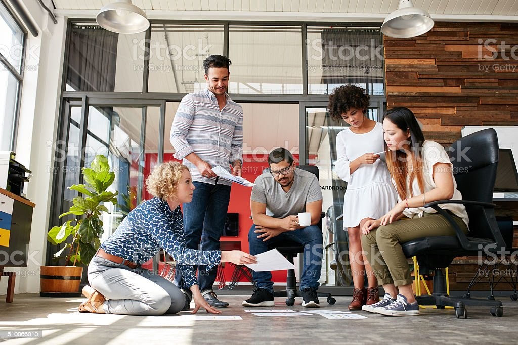 Designers planning layout on floor of office stock photo