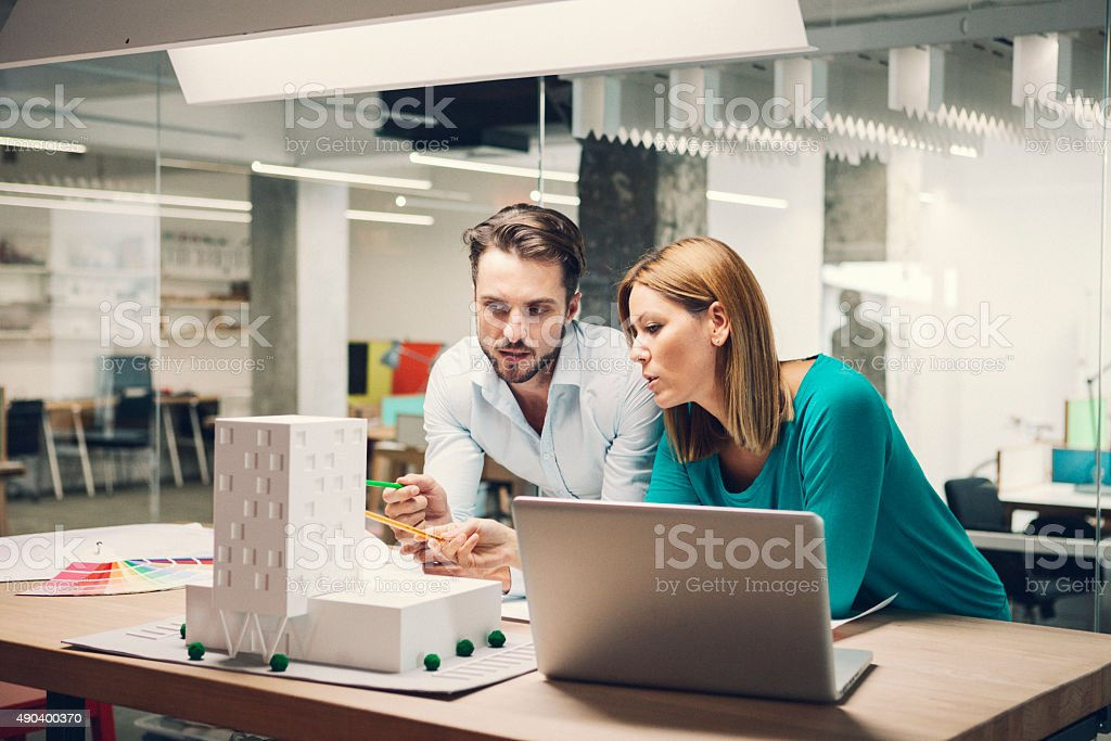 Designers reviewing architectural model in the office. stock photo