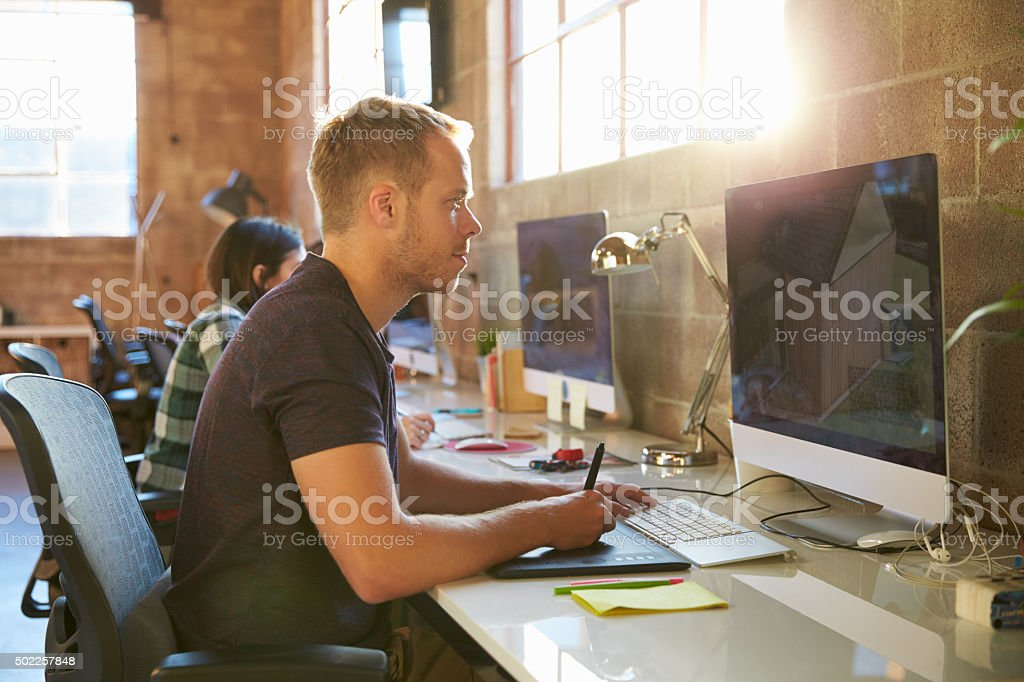 Designers Working At Desks In Modern Office stock photo