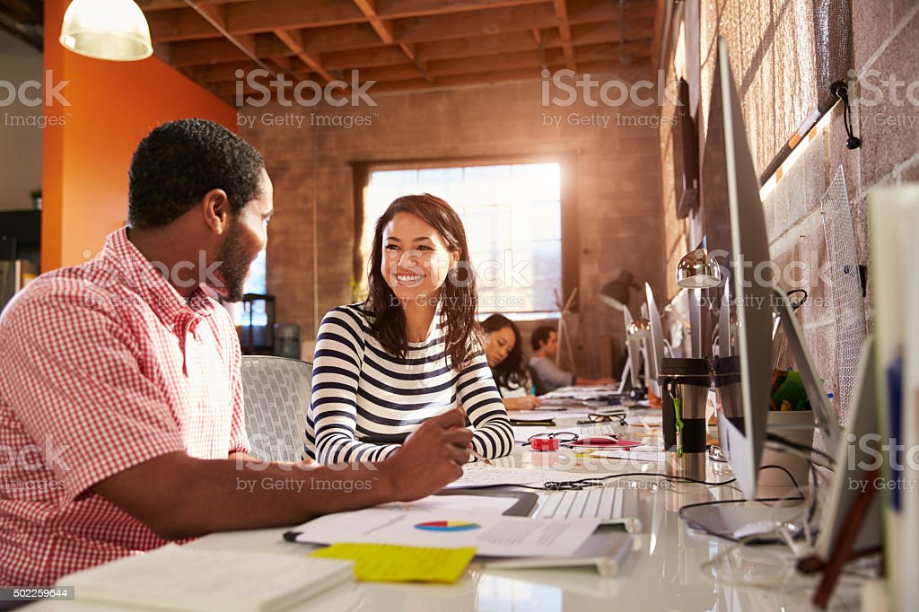 Designers Working Together At Desks In Modern Office stock photo