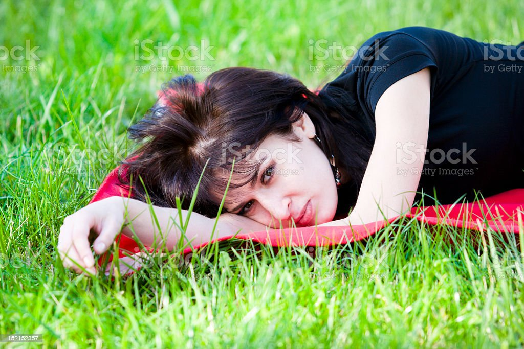 Desired nice beautiful tired woman relaxing on grass in park stock photo