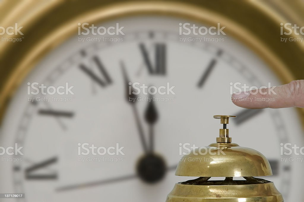 Desk Bell with a wall clock in the background stock photo