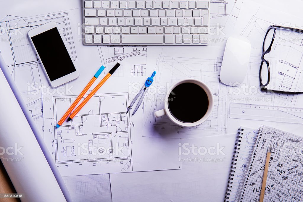 Desk, gadgets and housing projects. Flat lay. Wooden background. stock photo