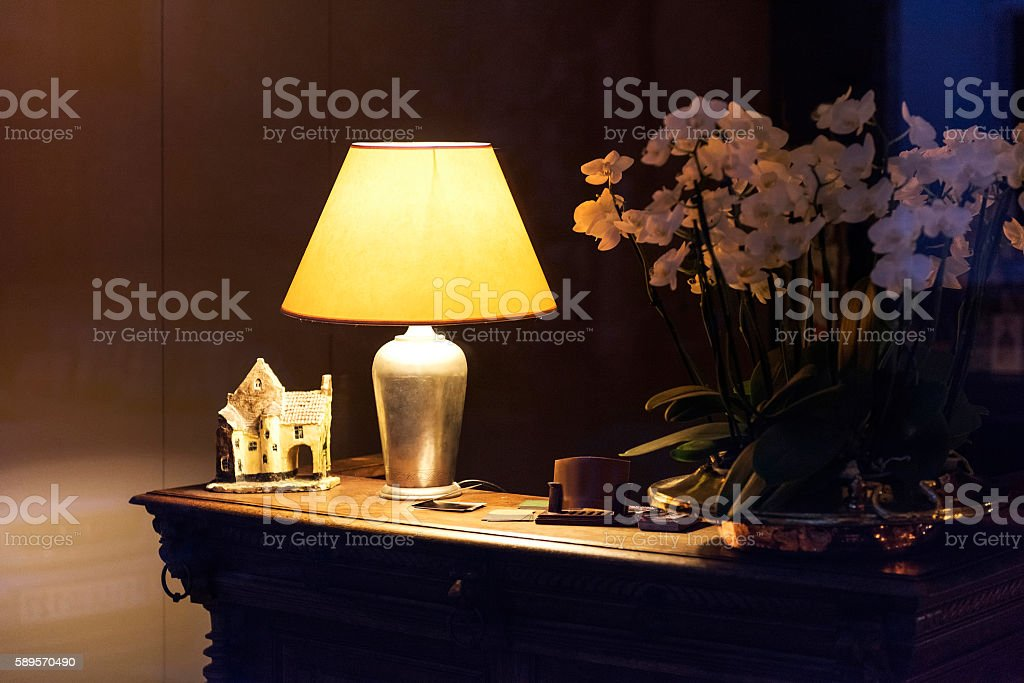 Lamp Shade and flowers on the wooden desk in Bruges, Belgium.