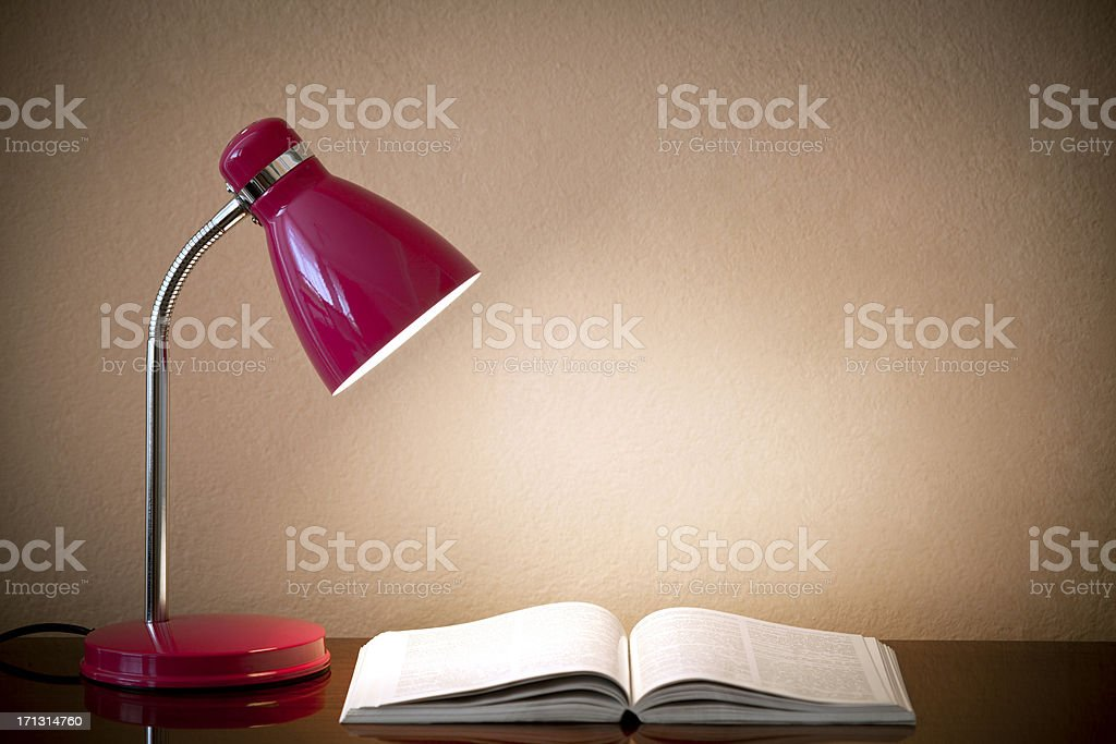 Desk lamp with an open book on the desk against a wall