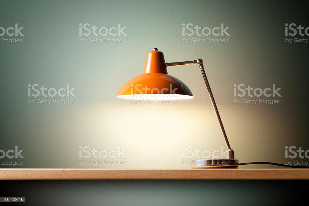 Retro orange desk lamp on the table.