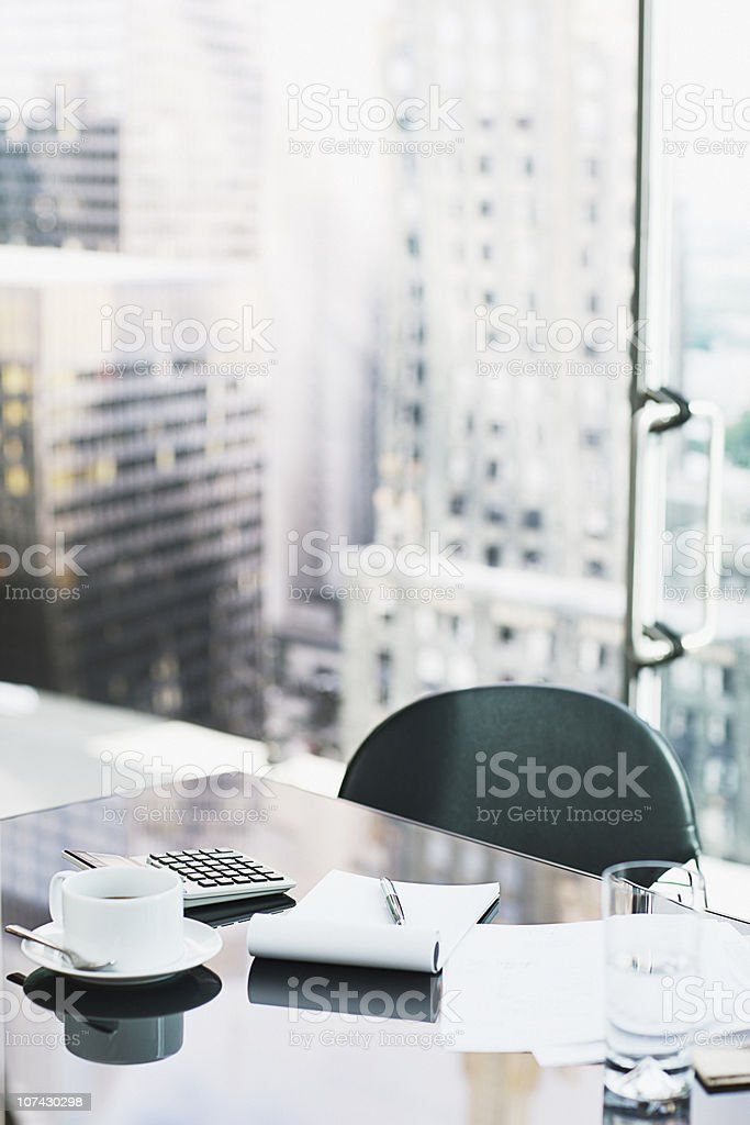 Desk with coffee, calculator, notepad and water royalty-free stock photo