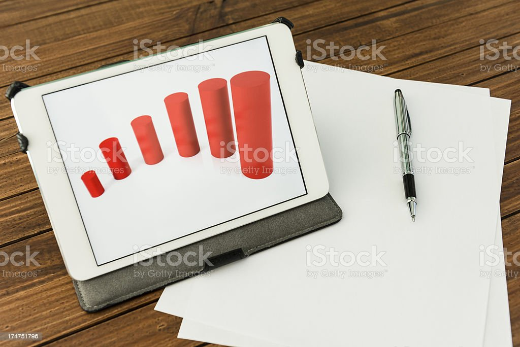 Desk with financial graph on digital tablet royalty-free stock photo