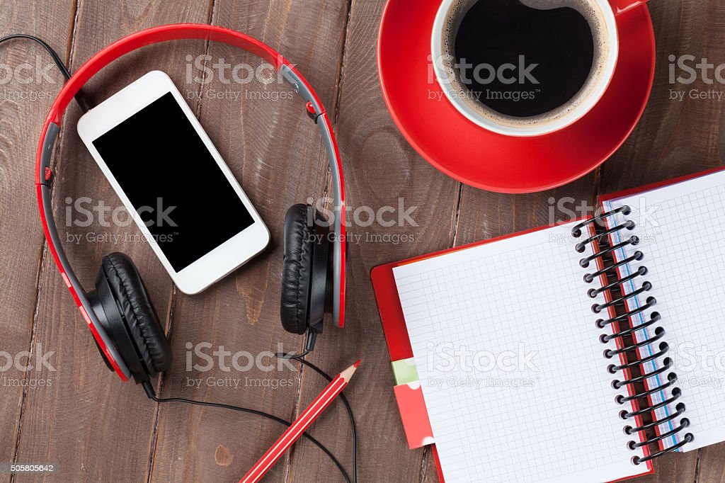 Desk with notepad, coffee, smartphone and headphones stock photo