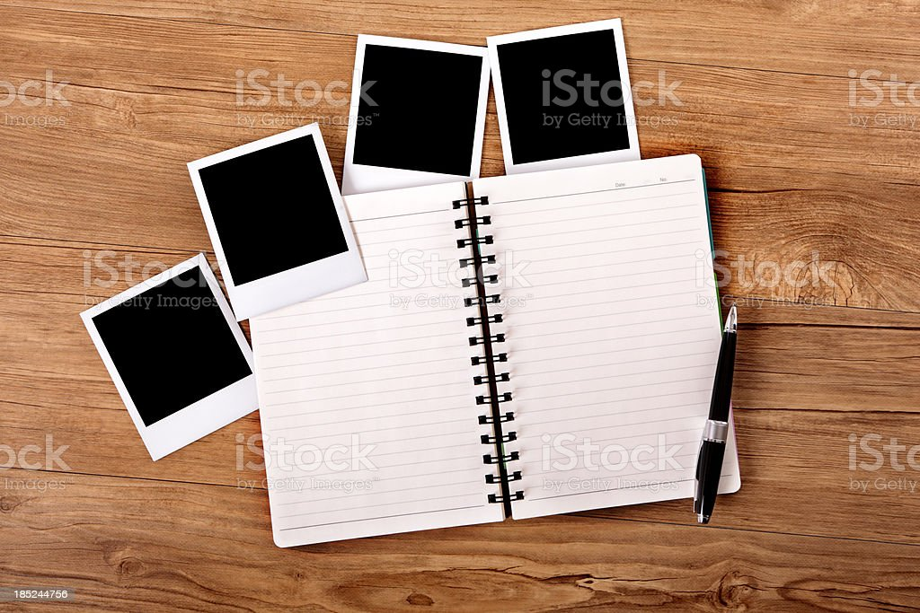 Desk with open notebook and blank photos. royalty-free stock photo