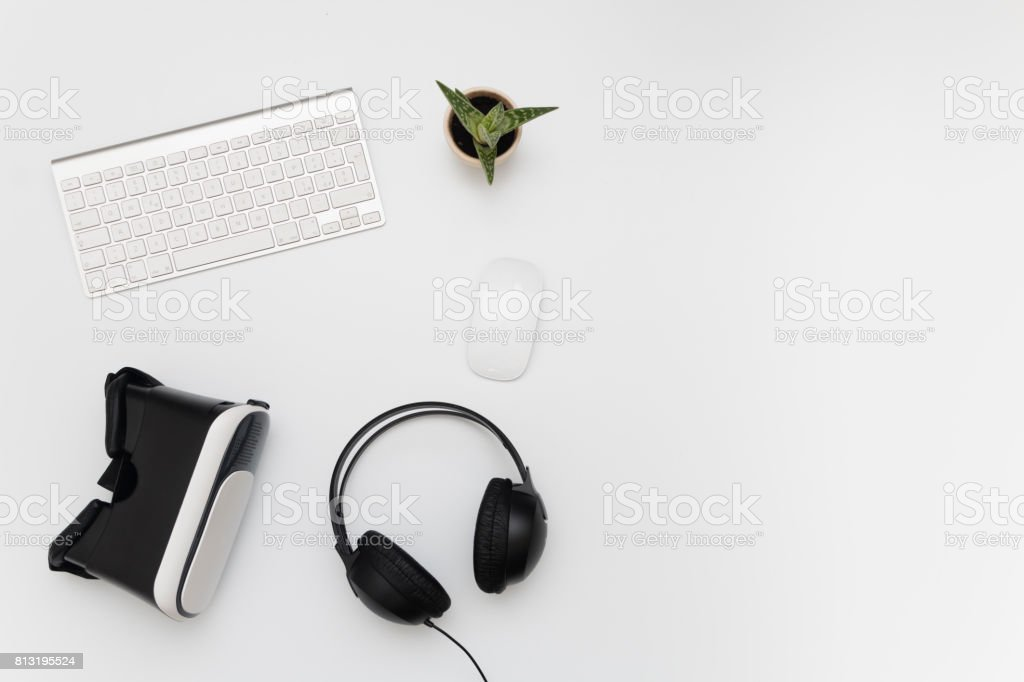 Desk with virtual reality device, heaphones, keyboard mouse and a fat plant stock photo