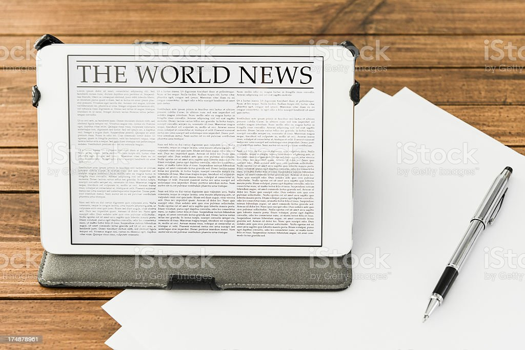 Desk with World news on digital tablet - New york royalty-free stock photo