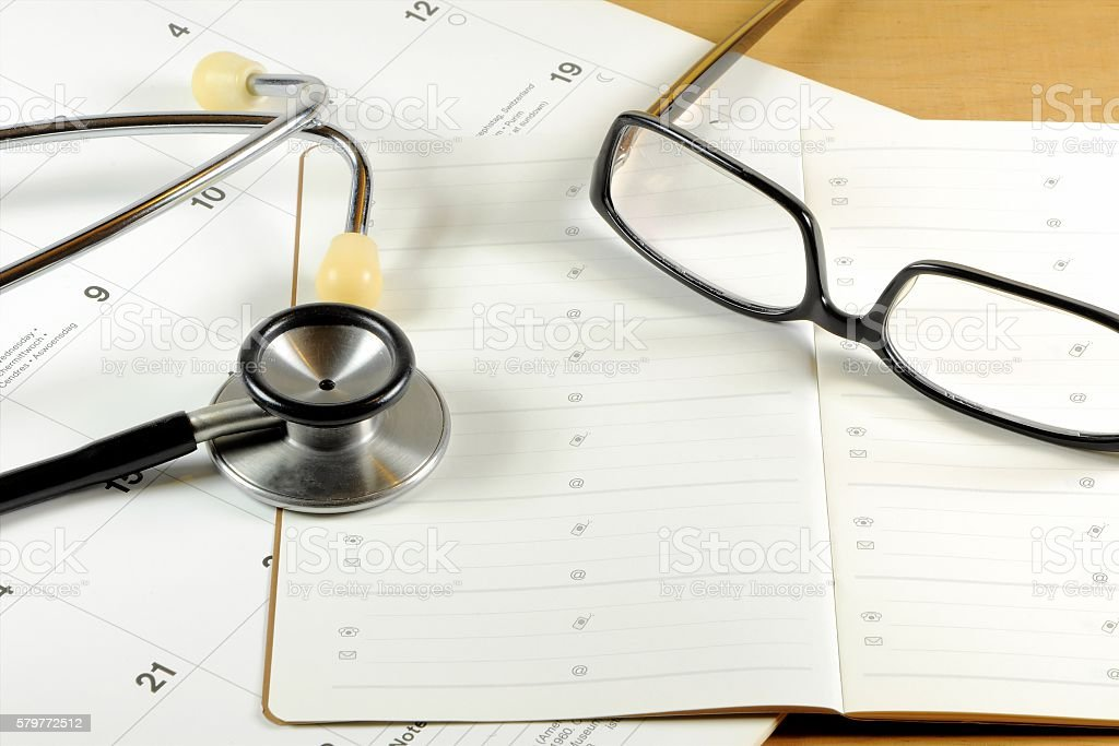 Desktop with stethoscope, address book, glasses and calendar stock photo