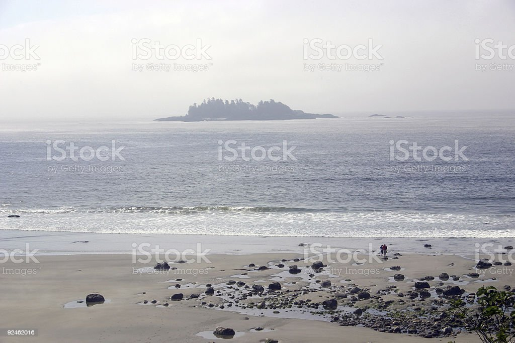 Desolate beach with tiny people stock photo