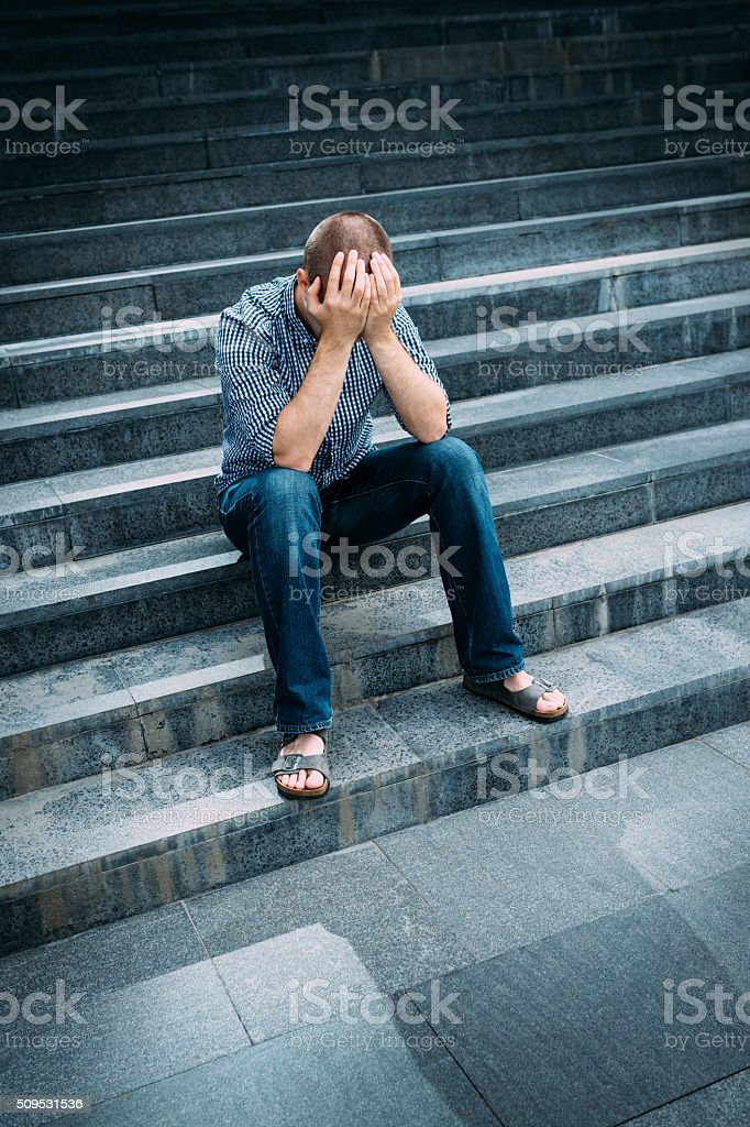 Despaired man covering his face with hands sitting on stairs stock photo