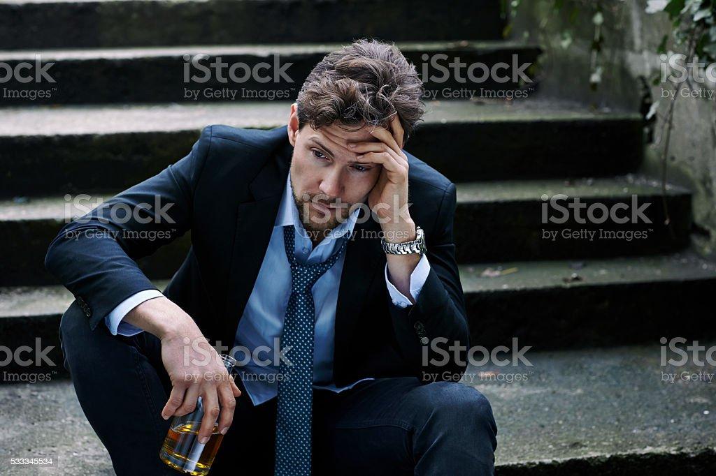 Despairing businessman holding bottle on steps stock photo