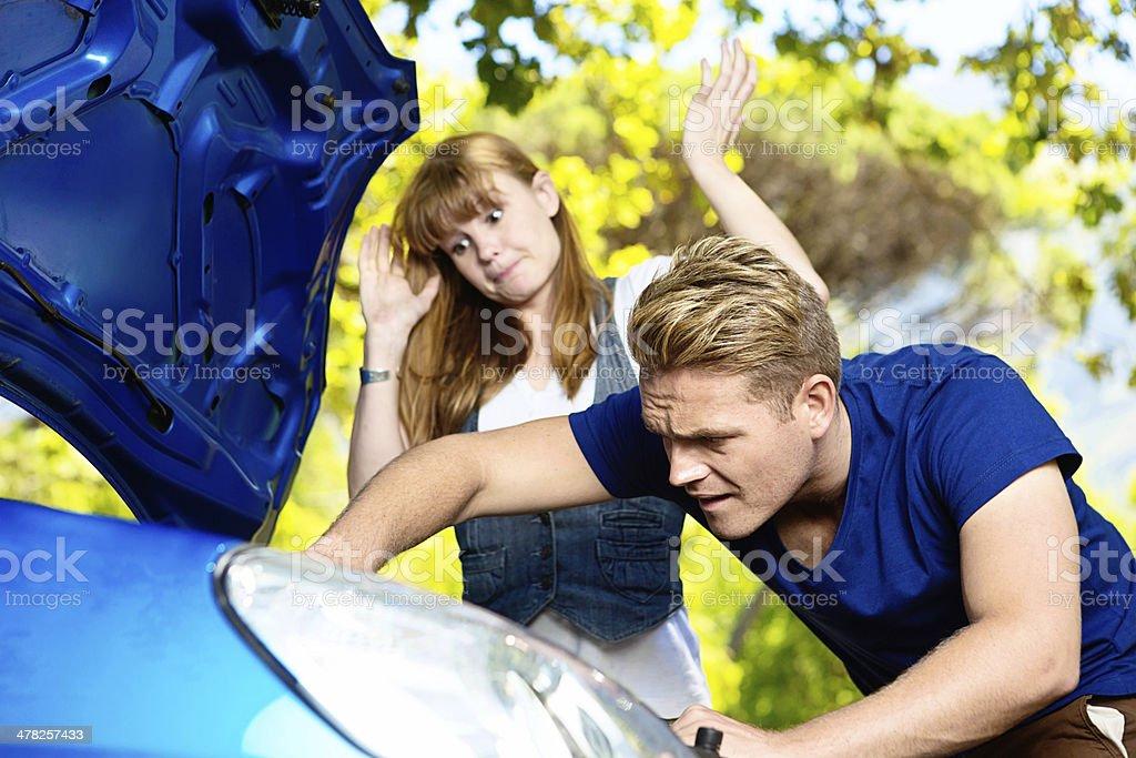 Despairing young woman watching man failing to fix her car stock photo
