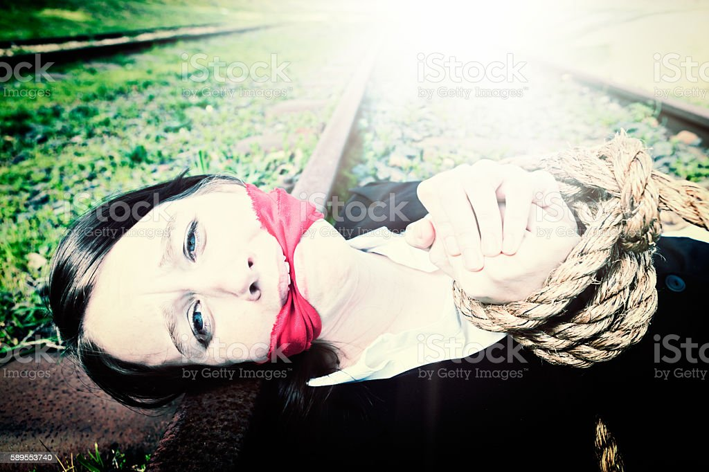 Desperate bound and gagged businesswoman lying on railroad track stock photo