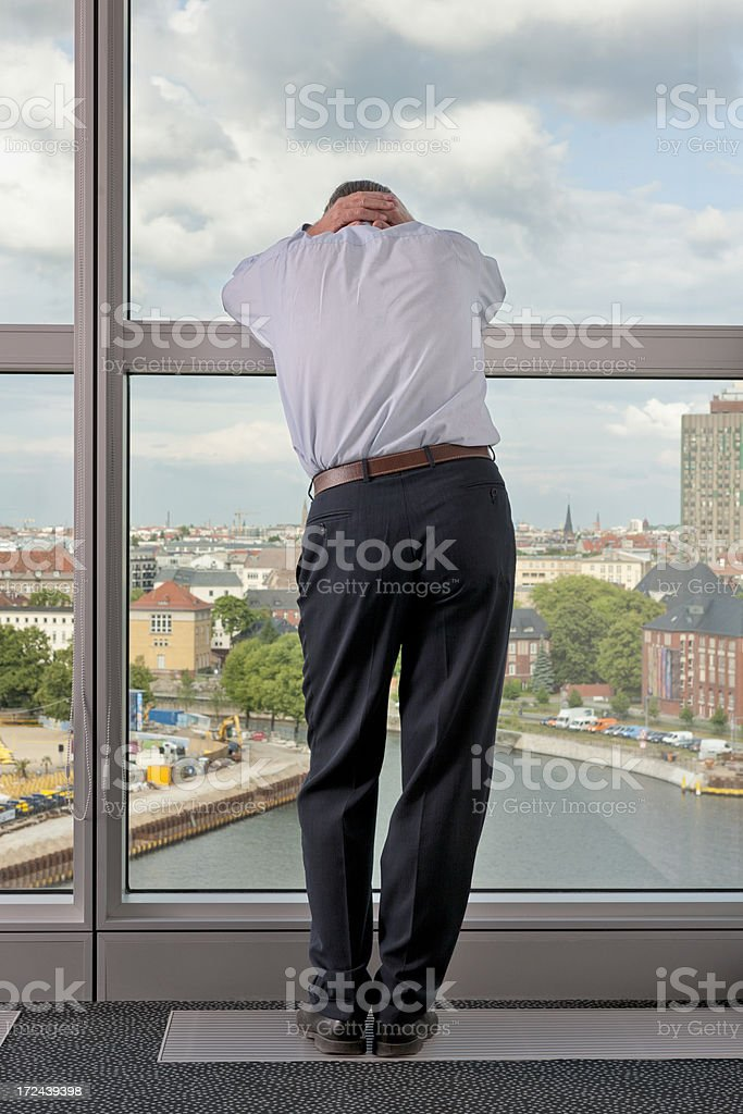 desperate businessman leaning on window frame royalty-free stock photo