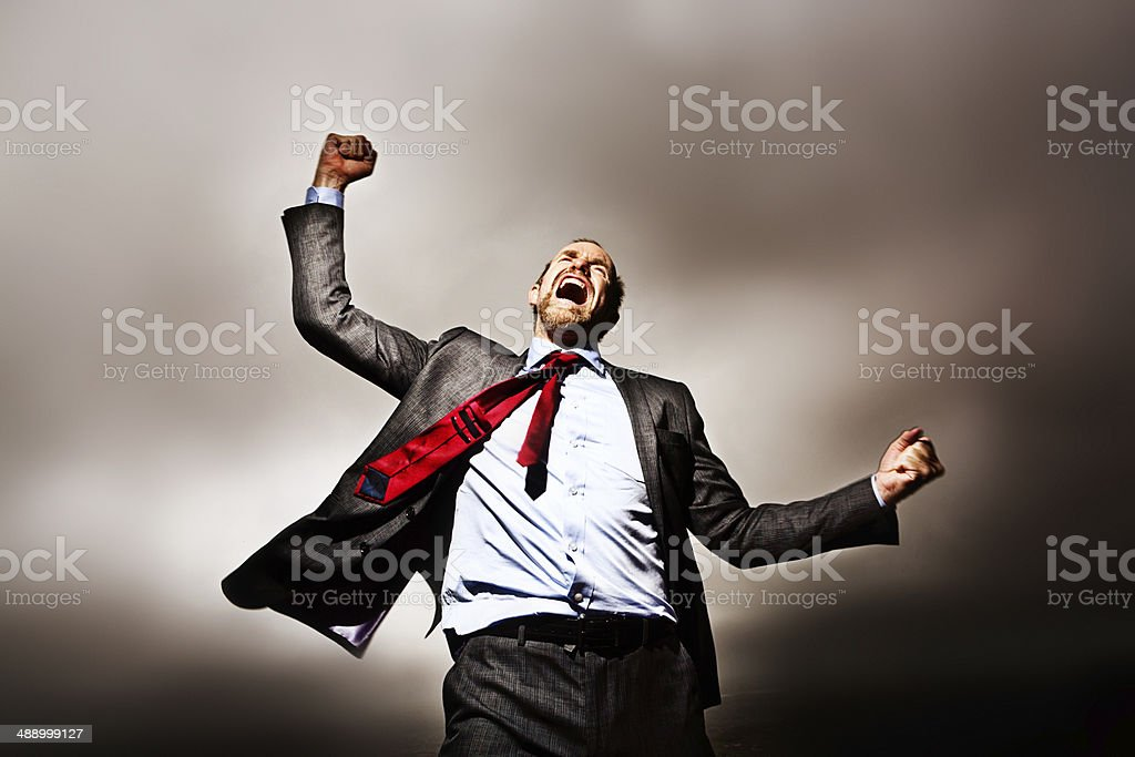 Desperate businessman on mountaintop shakes fists, raging against his fate stock photo