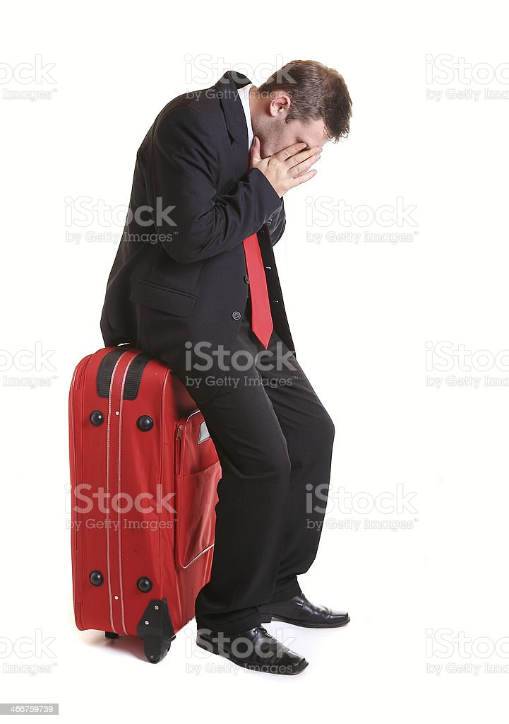 Desperate businessman sitting on red luggage stock photo