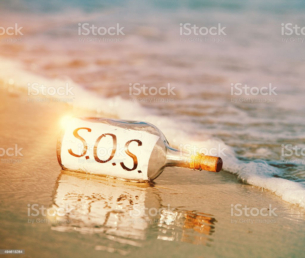 Desperate call for help: 'S.O.S.' message in bottle on beach stock photo