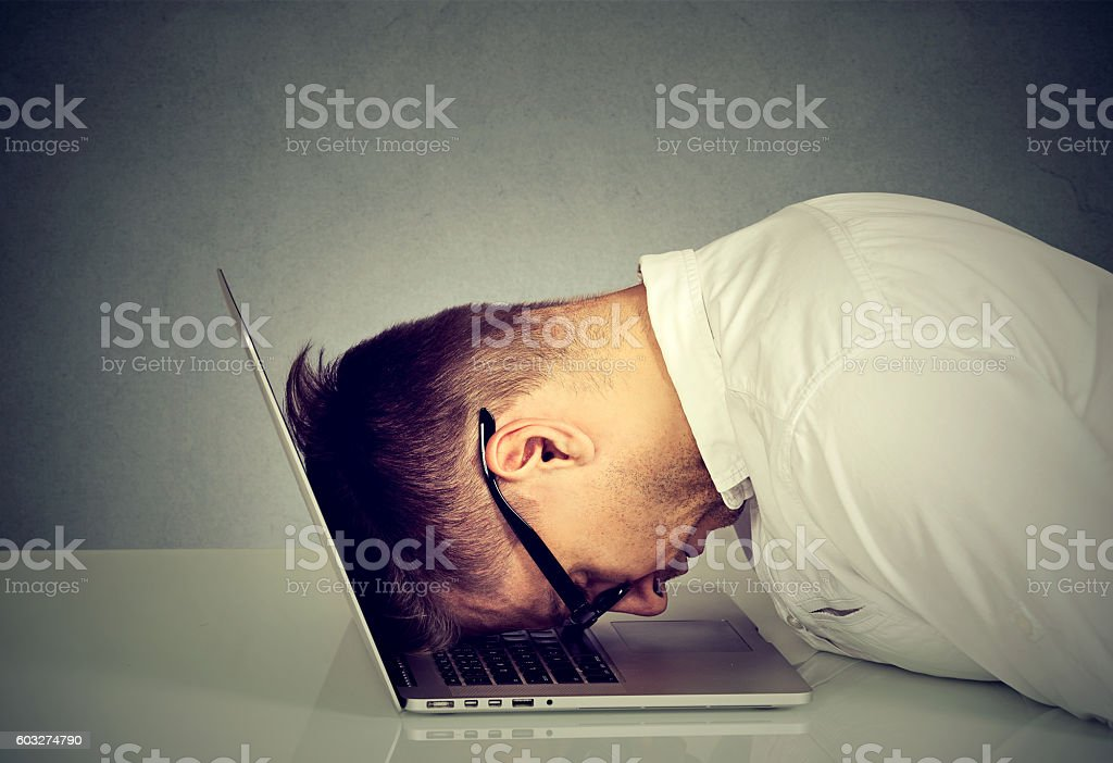 Desperate employee stressed man resting head on laptop stock photo