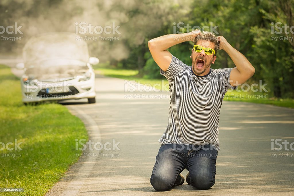 Desperate guy kneeing on the road because of broken car stock photo