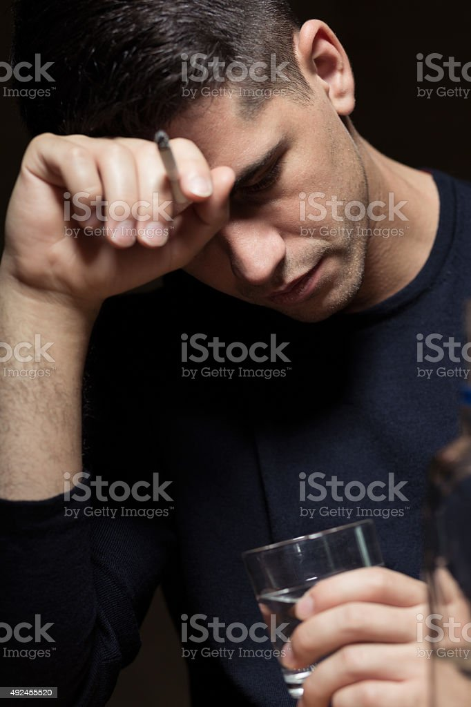 Desperate man abusing alcohol stock photo
