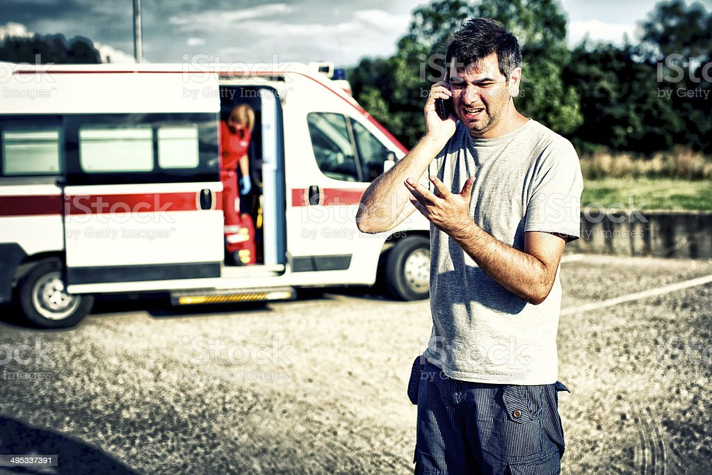 Desperate man at phone after an accident stock photo